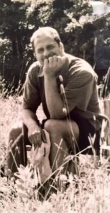 Bill Buczinsky sitting among tall grass.
